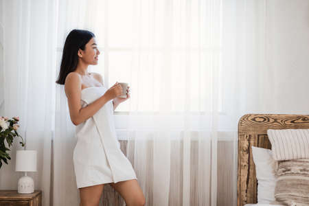 Asian girl in towel drinking coffee and looking through window at bedroom, empty space