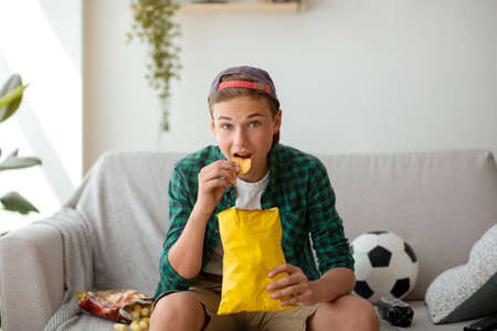 Concentrated teen guy eating chips and watching football game on TV at home Stockfoto
