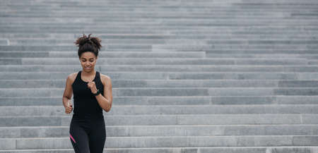 Strong athletic woman is running. Happy african american muscular girl in sportswear with fitness tracker doing cardio workout on stairs, free space