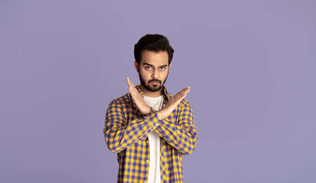 Handsome young Indian guy with crossed hands showing stop gesture on violet background. Panorama