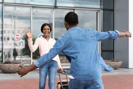 Happy african girl meeting her boyfriend after landing in airport, waving hand, ready to hug, selective focus Foto de archivo