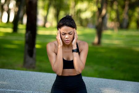 Black woman jogger having headache during training at public park, rubbing her head, copy space