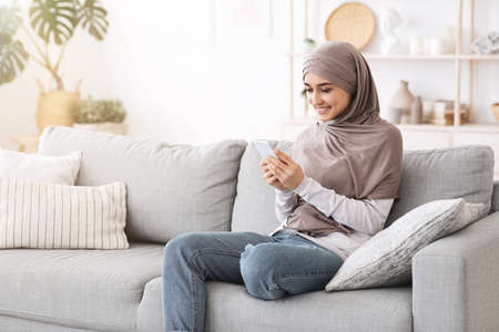 Modern Muslim Girl Using Smartphone At Home While Relaxing On Couch In Living Room, Texting With Friends Or Browsing Social Networks Foto de archivo