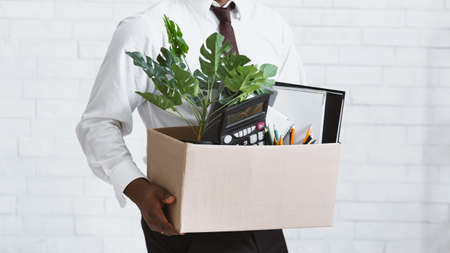 Losing job concept. Closeup view of African American guy with box of his stuff leaving office. Panorama