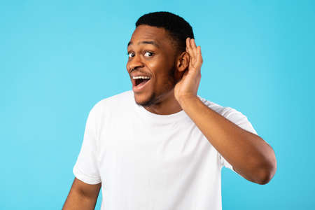 Positive African Man Listening Holding Hand Near Ear Posing On Blue Studio Background. Huh, I Hear You.
