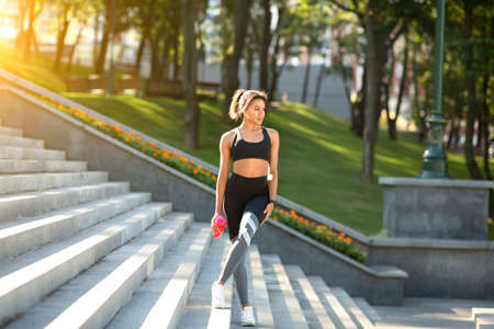 Pretty black fitness model in sport clothes posing in park, holding bottle with water, copy space