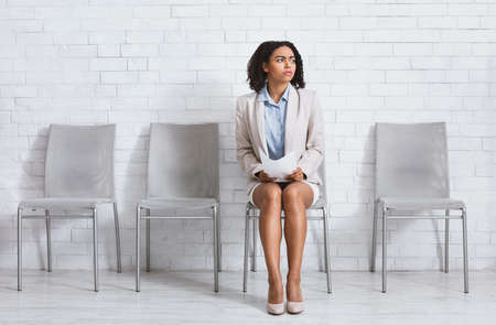 Worried black woman with CV waiting for work interview at company hall, empty space