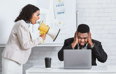 Angry African American lady boss with loudspeaker screaming at frightened male employee in office, panorama Banque d'images