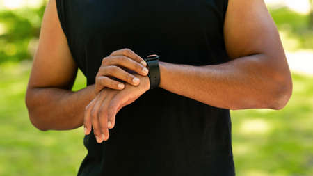 Cropped view of black guy checking his smartwatch or fitness tracker while working out outdoors, panorama