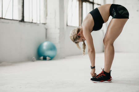 Flexion and exercise. Muscular adult woman in sportswear with fitness tracker working out in gym, copy space 写真素材
