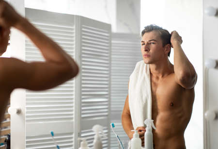 Focused man looking in mirror putting wax touching his hair styling or checking for hair loss problem 写真素材