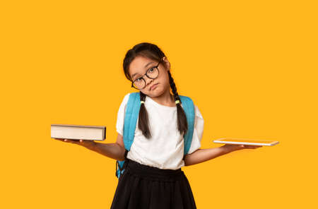 Puzzled Chinese Schoolgirl Comparing Digital Tablet And Book Posing In Studio Over Yellow Background. Books Vs Gadgets Concept
