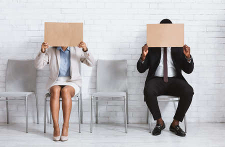 African American job applicants closing their faces with empty signs at company office, space for design