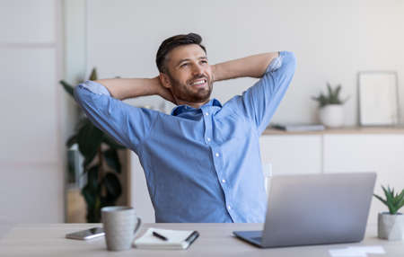 Smiling millennial businessman leaning back in chair at workplace, resting after successful day in office Stock Photo