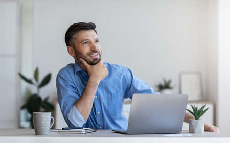 Pensive businessman sitting at workplace in modern office, thinking about new business idea, touching chin and looking aside with smile, free space