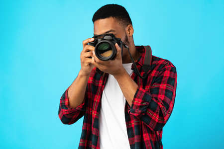 Photography Concept. African American Photographer Man Taking Photo Standing On Blue Background In Studio