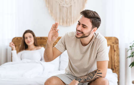 Solving problems in bed. Smiling man holding in hand and looking at blue pill, happy woman looking at husband in bedroom interior, free space Stock Photo