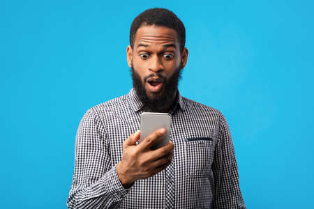 Portrait of emotional shocked black guy using cell phone, seeing surprising news, photos or message blue wall