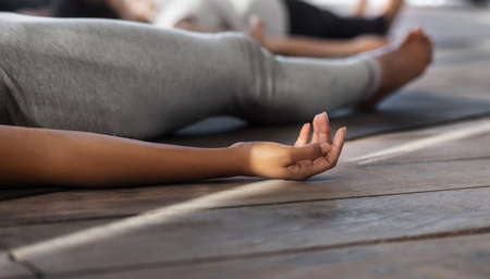 Unrecognizable black female practicing yoga in studio, lying in corpse pose, doing shavasana exercise, cropped image, closeup