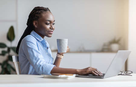 Morning Coffee At Work. Young black businesswoman enjoying hot drink while working on laptop in modern office, relaxing at workplace