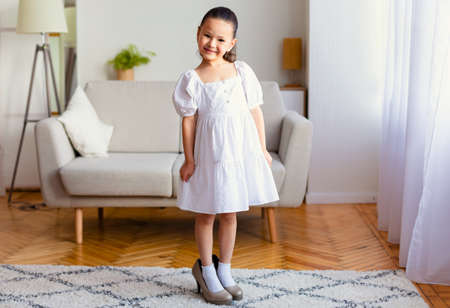 Adorable Asian Kid Girl Wearing Moms High Heels Shoes Posing Smiling To Camera Indoors. Childs Clothing And Style Concept