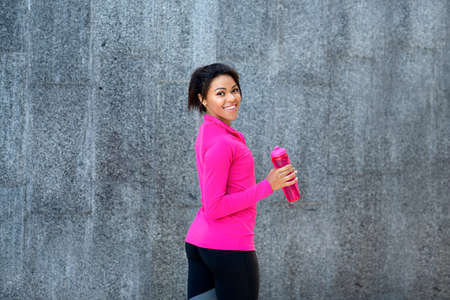 Cheerful black woman with bottle of water over gray wall at park, free space Stock fotó
