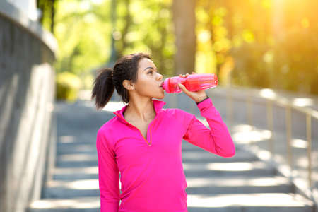 Thirsty sporty african girl drinking water, exercising at public park, sun flare Stock fotó