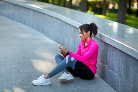Sporty black woman resting after training at park, using phone, empty space