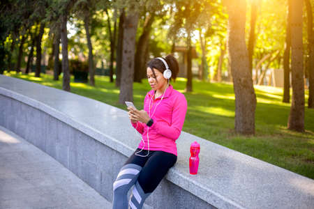 Athletic african american woman using phone, listening to music while training at park, free space