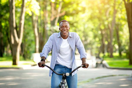 Happy black guy enjoying his bike ride at park in summertime