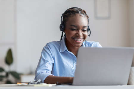 Hotline Support Service. Smiling african woman call center operator in headset working in modern office, free space