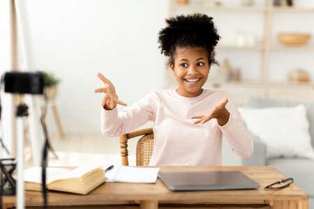 Little Blogger. African Teen Girl Making Video For Blog Sitting At Desk At Home. Selective Focus Banco de Imagens