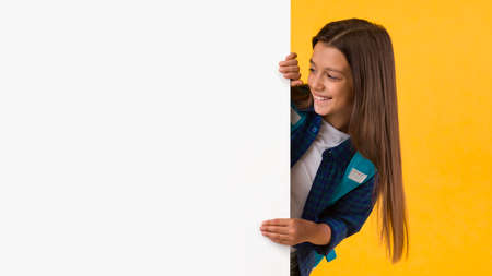 Glad little girl hiding behind blank white advertising billboard with copy space and peeking out, looking at board