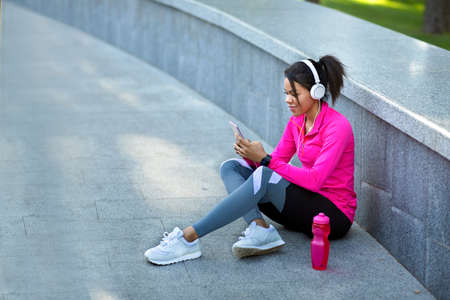 Black girl listening to music, using smartphone and headset, resting while jogging at park, copy space