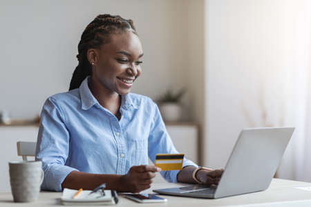 Young black businesswoman shopping online with laptop in office, using credit card to pay, transfering money, copy space