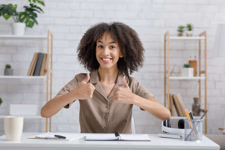 Good work at home office. Happy african american woman showing thumbs up at camera in living room interior