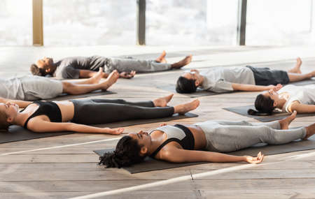 Group of sporty people relaxing during yoga lesson, lying on floor in Corpse pose, doing Shavasana, free space Stock Photo