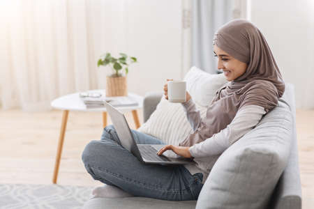Domestic Relax. Smiling Muslim Woman Using Laptop And Drinking Tea At Home, Sitting On Comfortable Sofa, Enjoying Free Time