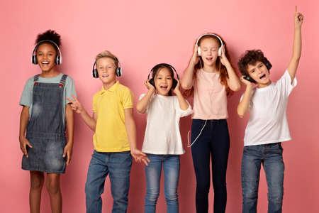 Multiethnic schoolchildren in headphones listening to music or audio books on pink background Stock Photo