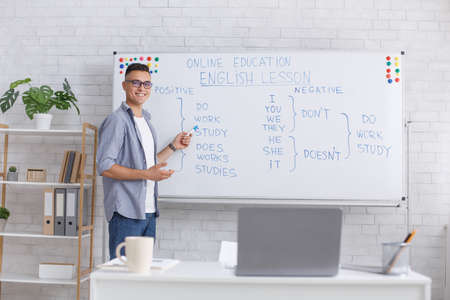 English lesson from home. Happy handsome guy with glasses points with marker to blackboard and explains rules in interior of living room, free space