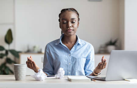 Coping With Stress At Work. Young African Businesswoman Meditating At Workplace In Office After Busy Day, Doing Breathing Exercises, Copy Space