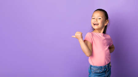Special Offer. Adorable asian girl pointing her finger at copyspace over pastel purple studio wall, banner