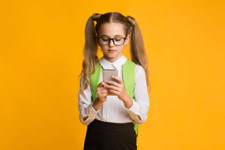 Schoolgirl Using Mobile Phone Playing Games Online Standing Over Yellow Studio Background. Kids And Gadget Addiction.