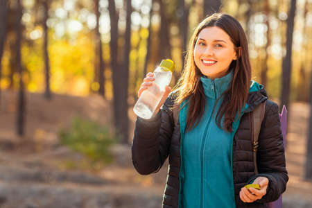Cheerful young woman backpacker drinking water and looking at camera, walking by forest, copy space Stock fotó