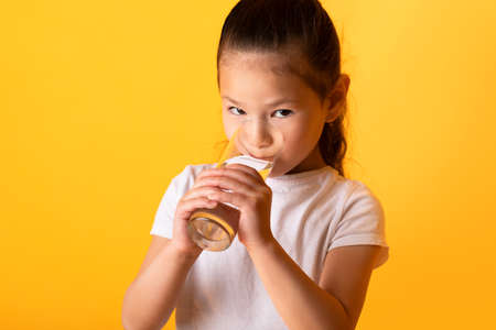 Healthcare Concept. Cute asian kid drinking mineral water from glass, looking at camera, yellow wall