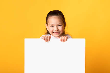 Advertisement Concept. Smiling little girl holding and looking out the square sign board with blank space, yellow wall