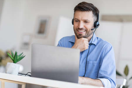Hotline Support Service. Handsome male call center operator in headset working with laptop in modern office, looking at computer screen, free space