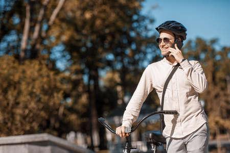 Safe bike ride. Smiling guy in helmet speaks by smartphone in park, in autumn, copy space