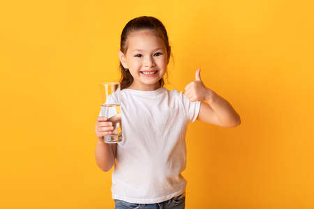Hydration Concept. Portrait of glad japanese girl standing with glass of fresh water gesturing thumb up, yellow wall Standard-Bild