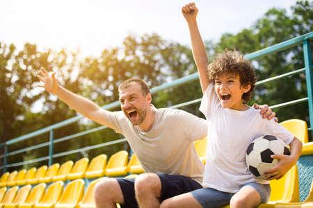 Goal. Emotional man and little boy cheering their favorite team, little boy holding soccer ball